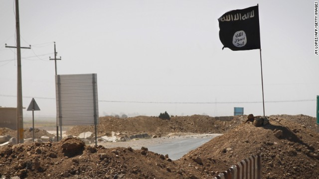 An ISIS flag flies on the other side of a bridge at the front line of fighting between ISIS and Kurdish Peshmerga fighters in Rashad, Iraq, on Thursday, September 11.