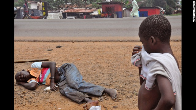 A child stops to look at a man who is suspected of suffering from Ebola on a main street in Monrovia, Liberia, on Friday, September 12.