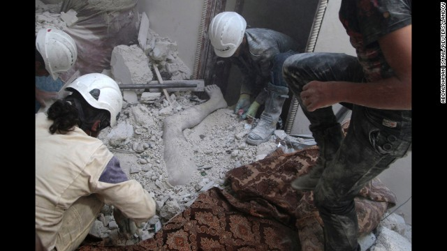 Residents of Aleppo remove a body from debris on Friday, August 29, after what activists claim was shelling by forces loyal to Syrian President Bashar al-Assad.