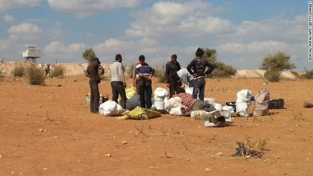Syrians fleeing the violence stand next to their belongings near the Syrian-Turkish border as they attempt to cross into Turkey on Sunday, September 7.