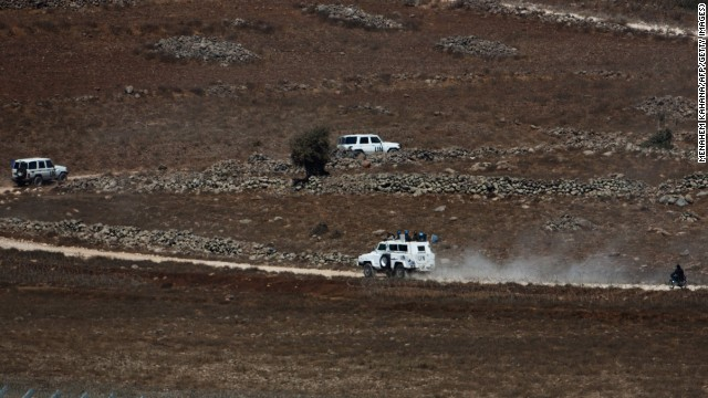 A U.N. convoy moves in the buffer zone near the Golan Heights as they are escorted by Syrian rebel fighters near the Syrian village of Jubata Al Khashab on Tuesday, September 2.