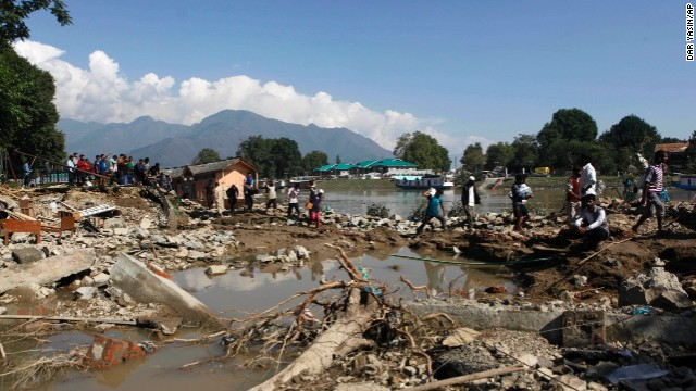 People walk past a breached bank of the River Jhelum in Srinagar on September 13.