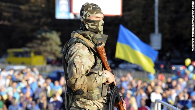 A Ukrainian soldier stands guard as residents rally in support of a united Ukraine in the southern Ukrainian city of Mariupol on September 13.