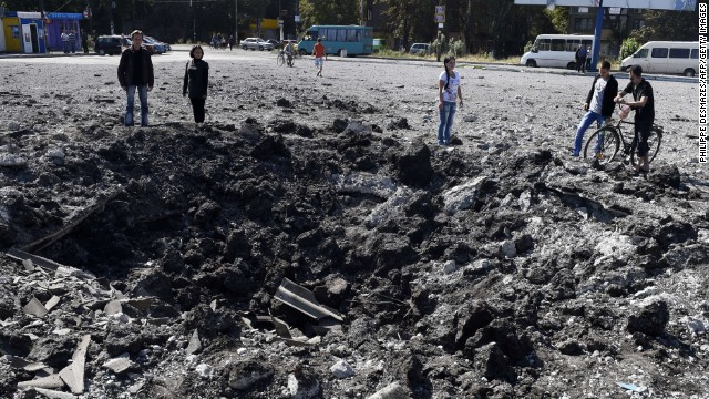 People look at a large crater on September 13 from a reported missile strike that hit a bus station the day before in Makiyivka, near Donetsk, eastern Ukraine.