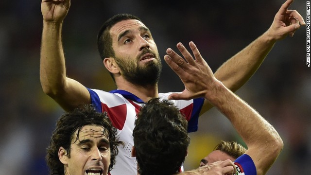 Arda Turan is hoisted skywards by his teammates after scoring Atletico Madrid's winner at the Bernabeu on Saturday.