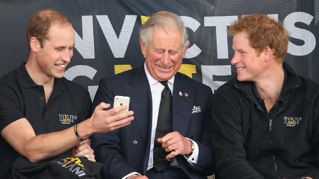 Prince William, Prince Charles and Prince Harry look at a mobile phone as they watch the Invictus Games on September 11, 2014, in London.