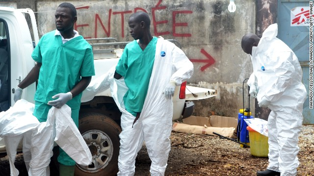 Members of a volunteer medical team wear protective gear before the burying of an Ebola victim Saturday, September 13, in Conakry.