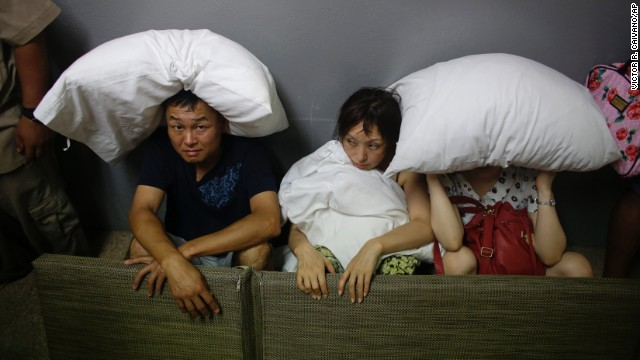 A family from San Jose, California, covers themselves with pillows as they sit in the service area of a Los Cabos resort on September 15.
