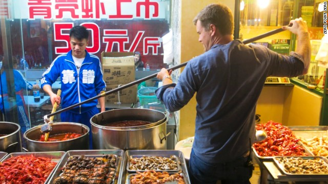 A cameraman gets an assist from a mounted GoPro for a close-up food shot in a Shanghai food stall.