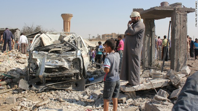 People in Raqqa, Syria, stand where a Syrian government aircraft was shot down by ISIS militants on Tuesday, September 16.