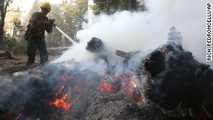 A U.S. Forest Service firefighter pours water on burning embers while clearing hot spots of the King fire in the El Dorado National Forest near Georgetown, Califronia, on Thursday, September 18.