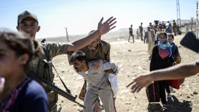 A elderly man is carried after crossing the Syria-Turkey border near Suruc on Saturday, September 20.