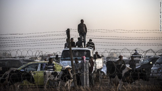 Syrian Kurds fleeing ISIS militants wait behind a fence in Suruc on Sunday, September 21.