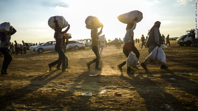 Syrian Kurds carry belongings as they cross the border between Syria and Turkey on September 20.