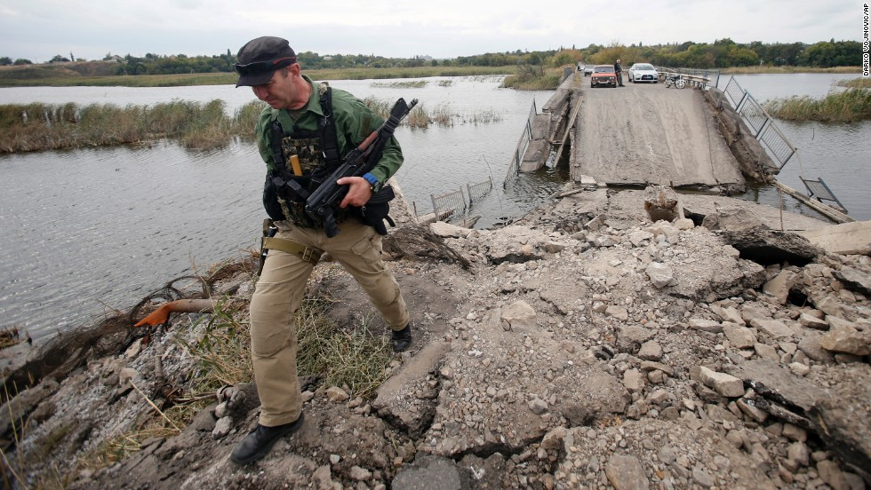 A pro-Russian rebel guards a destroyed bridge in Nyzhnya Krynka, Ukraine, on Tuesday, September 23. Fighting between Ukrainian troops and rebels in the country has left more than 3,000 people dead since mid-April, according to the United Nations.
