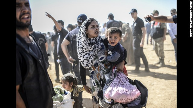 A Kurdish woman fleeing ISIS militants in Syria crosses into Suruc, Turkey, on Tuesday, September 23.