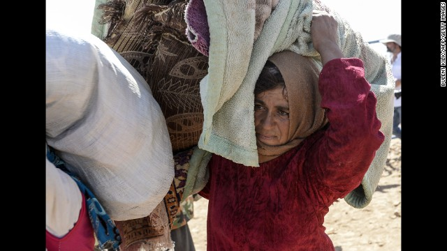 A woman carries belongings across the border between Turkey and Syria on September 23.