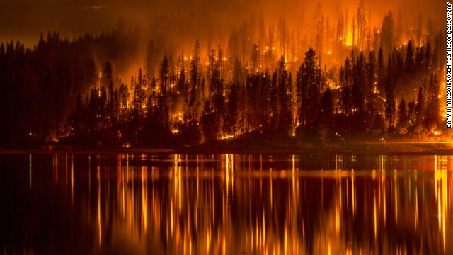 <strong>Wildfires:</strong> There's not a direct link between climate change and wildfires, exactly. But many scientists believe the increase in wildfires in the Western United States is partly the result of tinder-dry forests parched by warming temperatures. This photo shows a wildfire as it approaches the shore of Bass Lake, California, in mid-September.