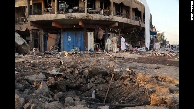 People inspect the aftermath of a car bomb attack in Baghdad on Tuesday, September 23.