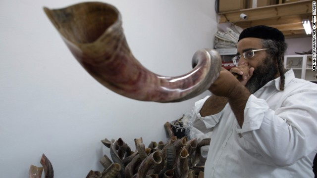 An Ultra-Orthodox Jewish man tests a shofar before buying it at a factory in Tel Aviv.