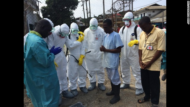 "MONROVIA, LIBERIA: A prayer before the dead body management team winds its way through the city's slums to retrieve cadavers. The number of Ebola cases in Liberia and Sierra Leone could rise to between 550,000 and 1.4 million by January if there are no ""additional interventions or changes in community behavior,"" the Centers for Disease Control and Prevention said in a report Tuesday. FULL STORY AT CNN.COM. Photo by CNN's John Bonifield."