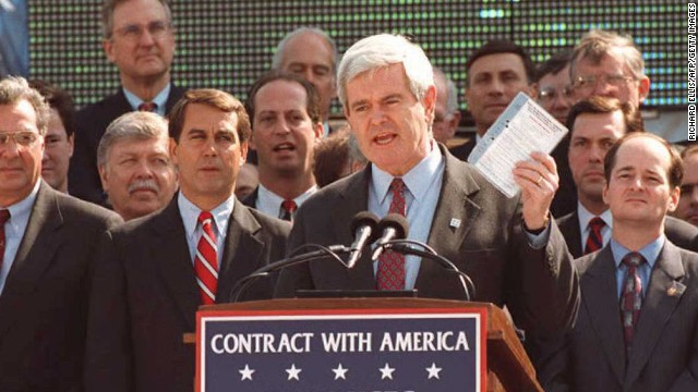 Newt Gingrich, speaker of the house in 1995, holds up a copy of the Contract With America on the steps of the U.S. Capitol.