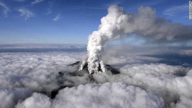 An aerial view shows the dense white plume of Mount Ontake rising high into the sky.