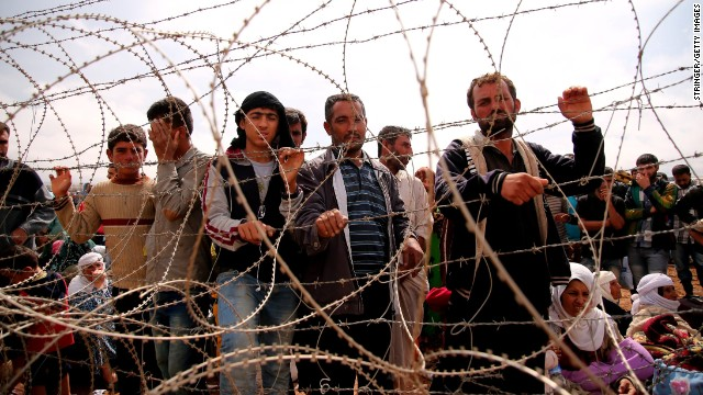Syrian Kurds wait behind border fences to cross into Suruc, Turkey, on Sunday, September 28.