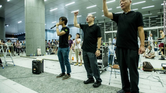 Benny Tai, center, founder of the Occupy Central movement, raises a fist after announcing the group would join the students during a demonstration outside government headquarters in Hong Kong on September 28.