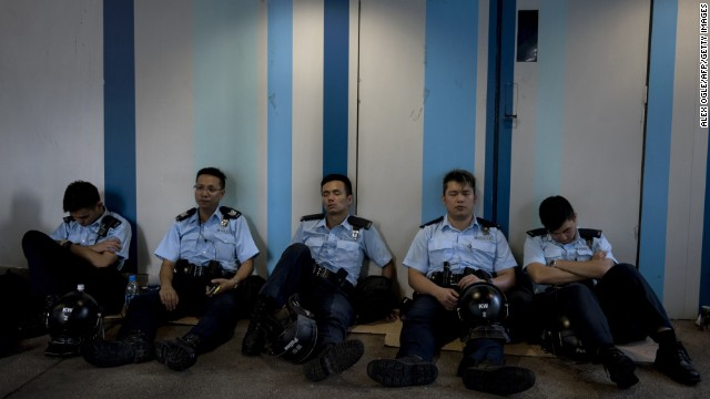Police officers rest near the government headquarters in Hong Kong on September 28.
