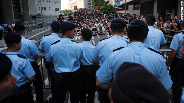 Pro-democracy protesters sit in a road as they face off with local police on September 29.