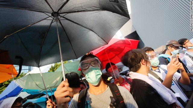 "SEPTEMBER 29 - HONG KONG: Pro-democracy activists use umbrellas to shield themselves from tear gas, prompting many to dub the protest movement the ""umbrella revolution."" The goal of the largest protests since the 1997 handover is to <a href='http://edition.cnn.com/2014/09/29/world/asia/china-hong-kong-protests/index.html?hpt=hp_t1'>pressure China into giving the former British colony full universal suffrage</a>."