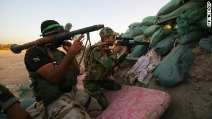 Iraqi Shiite militiaman aim their weapons during clashes with ISIS militants on Sunday, September 28, in Jurf al-Sakhar, 43 miles south of Baghdad.