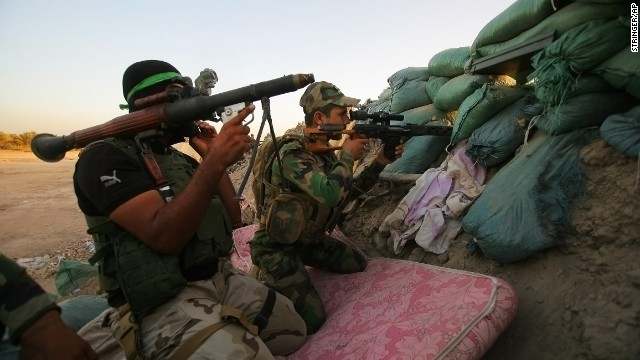 Iraqi Shiite militiamen aim their weapons during clashes with ISIS militants in Jurf al-Sakhar, Iraq, on Sunday, September 28.
