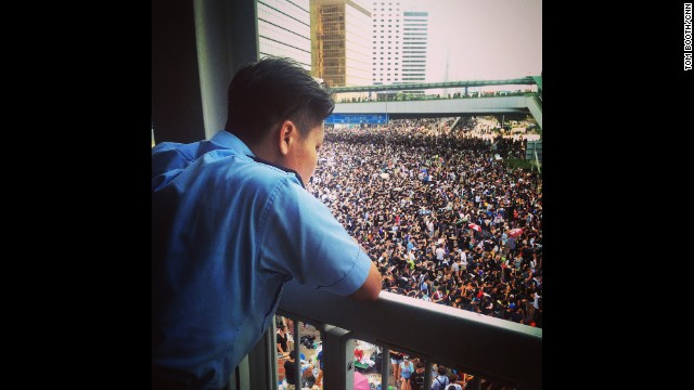 "HONG KONG: ""A police officer quietly observes the thousands of protesters joining the crowds in central Hong Kong."" - CNN's Tom Booth, September 29. Hong Kong is being gripped by pro-democracy protests. Demonstrators are angry at China's decision to allow only Beijing-vetted candidates to stand in the city's elections for chief executive in 2017. Follow Tom (@tboothhk) and other CNNers along on Instagram at instagram.com/cnn."