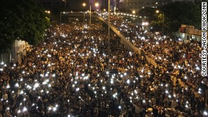 Photographed from above, the glowing screens of mobile phones held aloft by the sea of protesters\' have created an enduring image of solidarity.