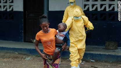 Marie Nyan, 26, whose mother died of Ebola, carries her 2-year-old son, Nathaniel Edward, to an ambulance after showing signs of the virus in the village of Freeman Reserve, about 30 miles north of Monrovia, Liberia, on Tuesday September 30.