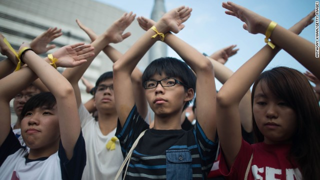 Founder of the student pro-democracy group Scholarism, Joshua Wong, center, stands in silent protest with supporters at the flag-raising ceremony at Golden Bauhinia Square in Hong Kong on October 1.