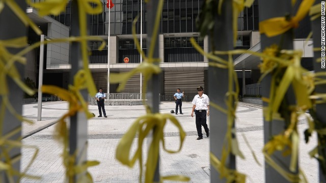 Yellow ribbons, a symbol of the protests in Hong Kong, are tied to a fence as police and security officers stand guard at the government headquarters on October 2.