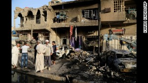 People inspect the site of a double car bombing in Baghdad, Iraq, on Wednesday, October 1.