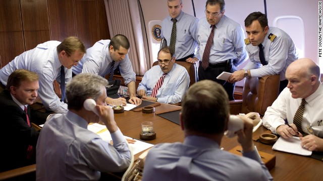 "Staff and U.S. Secret Service (USSS) discuss security measures aboard Air Force One during the flight from Istanbul, Turkey to Baghdad, Iraq. National Security Advisor Gen. James ""Jim"" Jones and Rahm Emanuel on phones, April 7, 2009. Special agent Joseph Clancy pictured on far right."