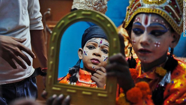 OCTOBER 2 - ALLAHABAD, INDIA: A young artist holds a mirror for another as they prepare for a traditional Ramleela drama, narrating the life of the Hindu God Rama, to celebrate the festival of Dussehra on October 1. The occasion commemorates the triumph of Lord Rama over the demon king Ravana, marking the victory of good over evil.