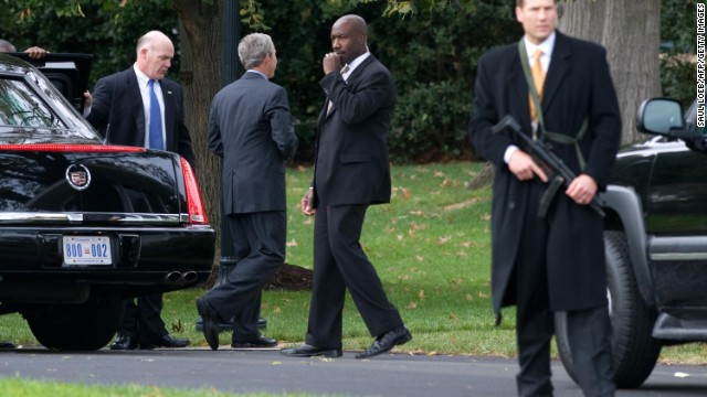 "Clancy's nickname for some members of the Secret Service is ""Father Joe."" Here he holds the door as George W. Bush (C) exits his limousine on the South Lawn of the White House in Washington, DC, after a security alert on the White House grounds, October 28, 2008."