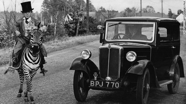 "Back in 1935, a motorist pauses as Laffin Leslie, 18, guides Jimmy, labeled ""The only rideable zebra in the world,"" across a road in Berkshire, England."