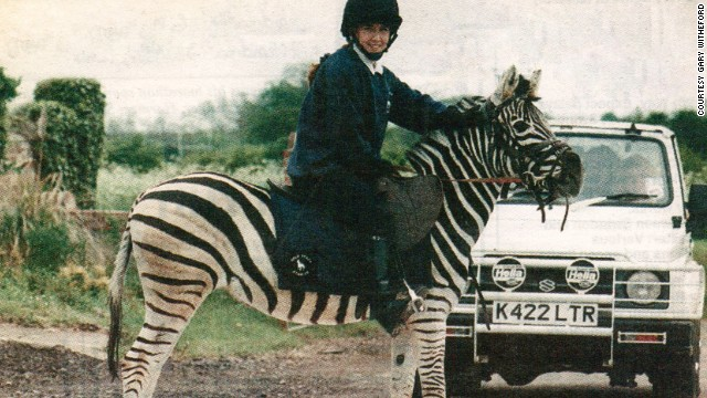 No, your eyes are not playing tricks. That is a girl riding a zebra.