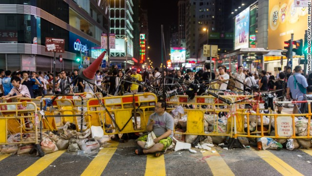 A man sits in front of a barricade built by pro-democracy protesters on October 4 in the Kowloon district of Hong Kong.