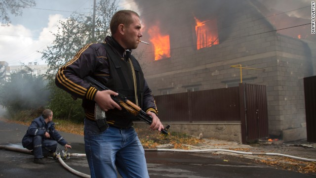 A pro-Russian rebel walks past a burning house after shelling in Donetsk on Sunday, October 5.