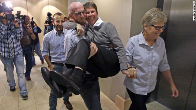 From left, plaintiffs Moudi Sbeity; his partner, Derek Kitchen; Kody Partridge; and Partridge's wife, Laurie Wood, celebrate after a news conference in Salt Lake City on Monday, October 6. The U.S. Supreme Court had just cleared the way for legal same-sex marriages in five more states -- Virginia, Utah, Nevada, Indiana and Wisconsin.