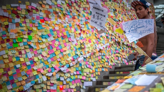 Post-it messages filled with sketches and messages cover a wall next to a stairway in the Admiralty district in Hong Kong. Some of them are words of hope, and others denounce the Hong Kong's top official, the chief executive.