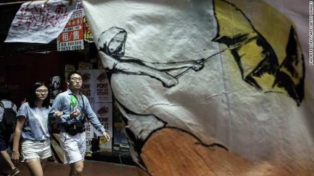 A couple walk past a banner of a man carrying a yellow umbrella, which has come to symbolize the protest.
